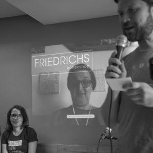 """Vier Menschen. Links sitzen zwei Frauen, die interessiert zusehen. Daneben eine Frau, die an die Wand projiziert wird. Mit im Bild das Logo von der Wand """"Friedrichs Coffeeshop"""". Rechts steht ein Mann, der in ein Mikrofon spricht. Vor ihm ein Handy auf einem Stativ, das ihn abfilmt."""